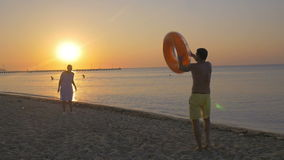Young couple playing with rubber ring at the. Slow motion clip of man and woman playing with big rubber ring on the beach. They throwing it to each other on the stock video footage
