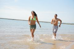Young Couple Playing and Runing by Water Front Royalty Free Stock Images