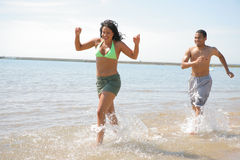 Young Couple Playing and Runing by Water Front Royalty Free Stock Photo
