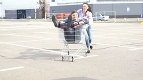 Young couple playing with a shopping trolley stock video footage