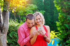 Young couple playing with smart phone in the park Stock Image