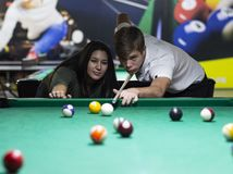 Young couple playing snooker together in bar royalty free stock images