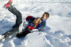 Young couple playing in the snow. Man and woman having fun wrestling in the snow Royalty Free Stock Image