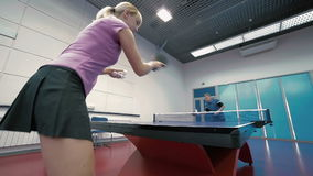 Young couple playing the table tennis at the court. Shooting from the down, woman in close-up. Young woman and man virtuosity playing a table tennis at the court stock video footage