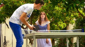 Young couple playing table tennis. Outdoors in the hotel. Woman wins and she is happy stock video