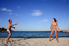 Young couple playing tennis on a beach. Young couple playing tennis on a beach during their vacation Royalty Free Stock Photos