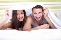 Young couple playing under the sheets Stock Images