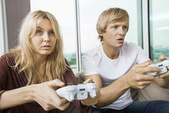 Young couple playing video game in living room at home Royalty Free Stock Images
