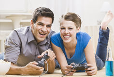 Young Couple Playing Video Games. A young couple playing video games.  They are smiling and laughing, and are lounging on the floor. Horizontally framed photo Royalty Free Stock Photos