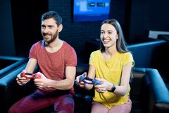 Couple playing video games with gaming console in the club stock photos