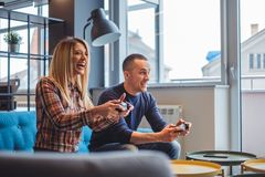 Young couple playing video games and smiling. Beautiful young couple playing video games and smiling in the living room Stock Image
