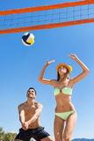 Young couple playing volleyball. On the beach. Focus on man royalty free stock image