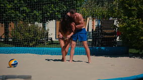 Young couple playing volleyball on the beach and girl fall down on the sand. Young couple playing volleyball on the beach near the net. The guy throw the ball to stock video footage