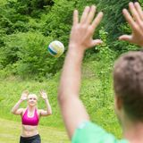 Young couple playing volleyball in park. Royalty Free Stock Images