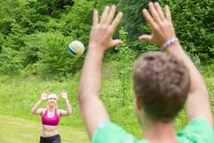 Young couple playing volleyball in park. Stock Image