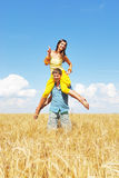 Young couple playing on wheat sunny field Stock Images
