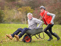 Young couple playing in wheelbarrow Stock Image