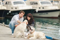 Young Couple Playing With A Dog In The Harbor Royalty Free Stock Images