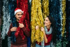 Young couple plays with holiday fluffy garland. Purchase of christmas decoration in supermarket, family tradition. December shopping stock images