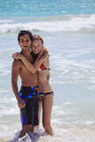 Young couple plays in the surf. A young couple plays at water's edge,hugging each other, by the surf at kailua Beach, Hawaii stock images