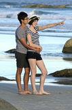 Young couple pointing along beach Stock Image