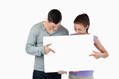 Young couple pointing at banner Stock Photos