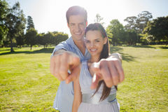 Young couple pointing finger to the camera at park Royalty Free Stock Photos