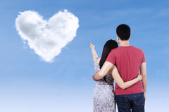 Young couple pointing at heart clouds Royalty Free Stock Image