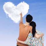 Young couple pointing at heart Stock Photography