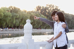 Young Couple Pointing by a Lake Stock Photography