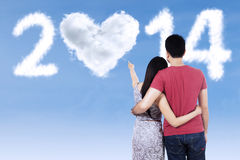 Young couple pointing at new future. Back view of young couple pointing at clouds shaped 2014 on the sky Stock Photo