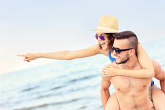 Young couple pointing at something at the beach Stock Photography