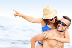 Young couple pointing at something at the beach Stock Photos