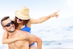 Young couple pointing at something at the beach Stock Photo