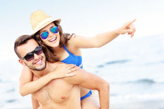 Young couple pointing at something at the beach Stock Image