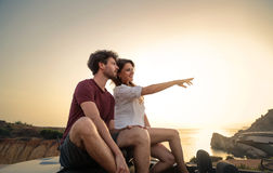 Young couple pointing at something. Young couple travelling by car, pointing something in front of them. Behind a beautiful landscape: sunset in the sea Stock Photo