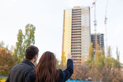 Young Couple Pointing Up at High Rise Building Royalty Free Stock Images