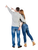 Young couple pointing at wal Back view  (woman and man). Stock Photo