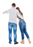 Young couple pointing at wal Back view  (woman and man). . Stock Photography