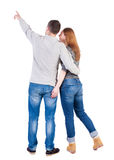 Young couple pointing at wal Back view  (woman and man). . Royalty Free Stock Photo