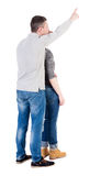 Young couple pointing at wal Back view  (woman and man). Royalty Free Stock Images