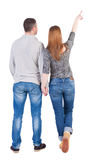 Young couple pointing at wall. Back view  (woman and man). Stock Images