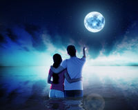 Young couple ponting moon at night time Royalty Free Stock Images