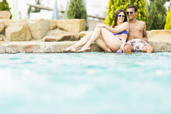 Young couple by the pool. Beautiful young couple men and women on summer holiday in swimming pool resort Royalty Free Stock Photo