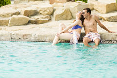 Young couple by the pool. Beautiful young couple men and women on summer holiday in swimming pool resort Stock Photography