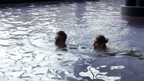 Young couple in pool chit chatting stock video