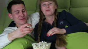 Young couple with popcorn watching comedy on television and laugh. stock video footage