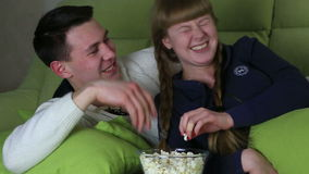 Young couple with popcorn watching comedy on television and laugh. stock video