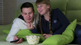 Young couple with popcorn watching comedy on television and laugh. stock footage