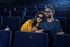 Young couple with popcorn watching movie stock images